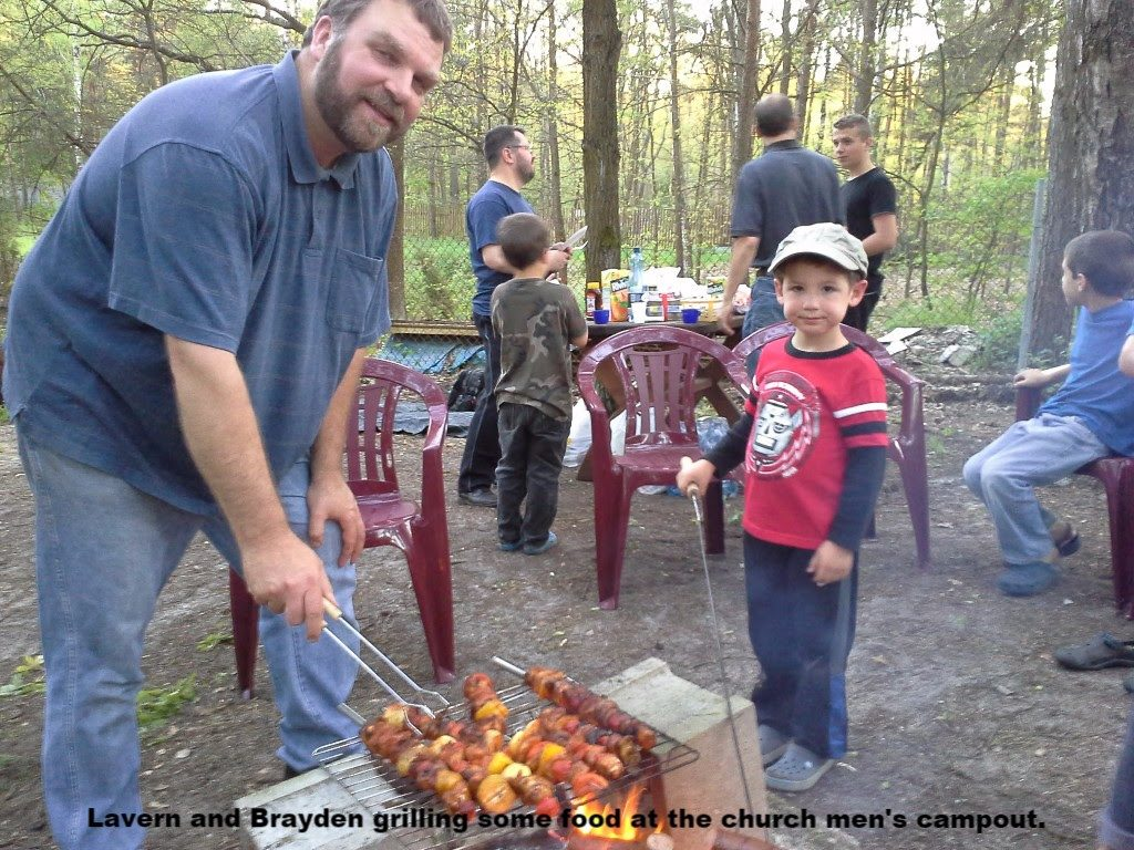 Lavern and Brayden grill food during the men and boys' campout